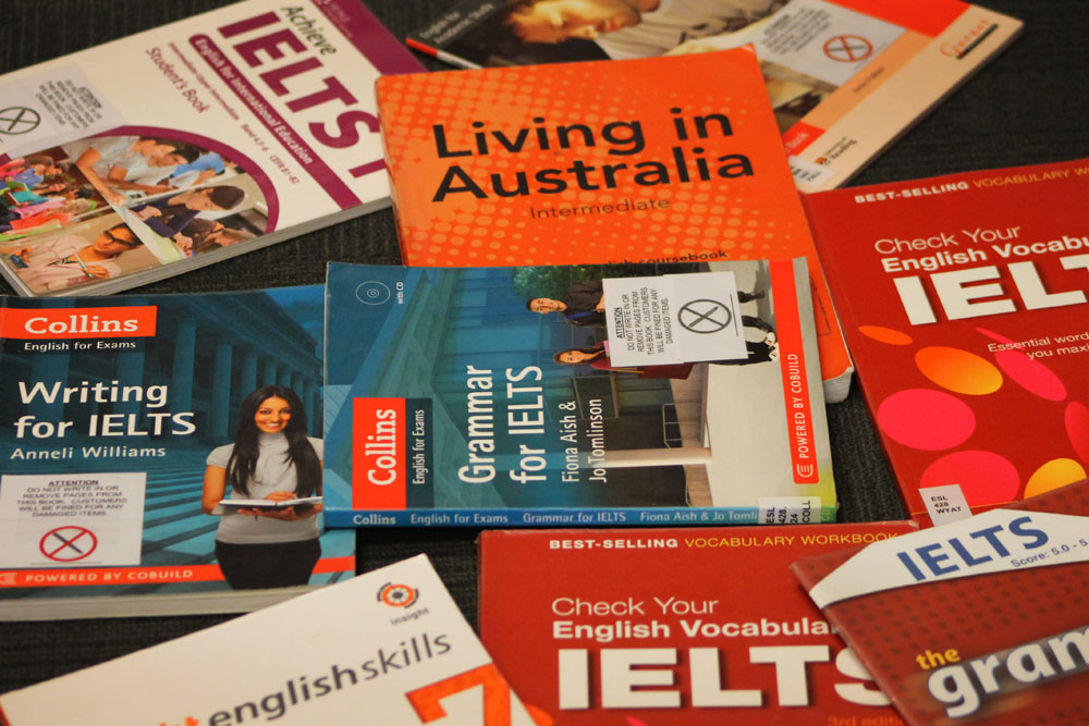 Multiple language learning books scattered across a surface