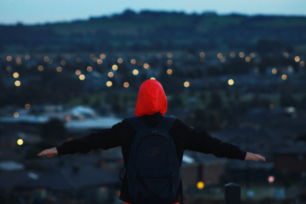 a young person in a red hood stands with arms outstretched before a skyline at dusk