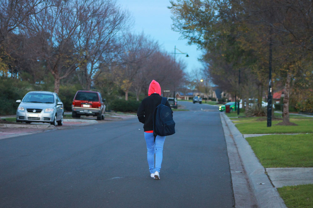 A person in a red hood walks down a suburban street
