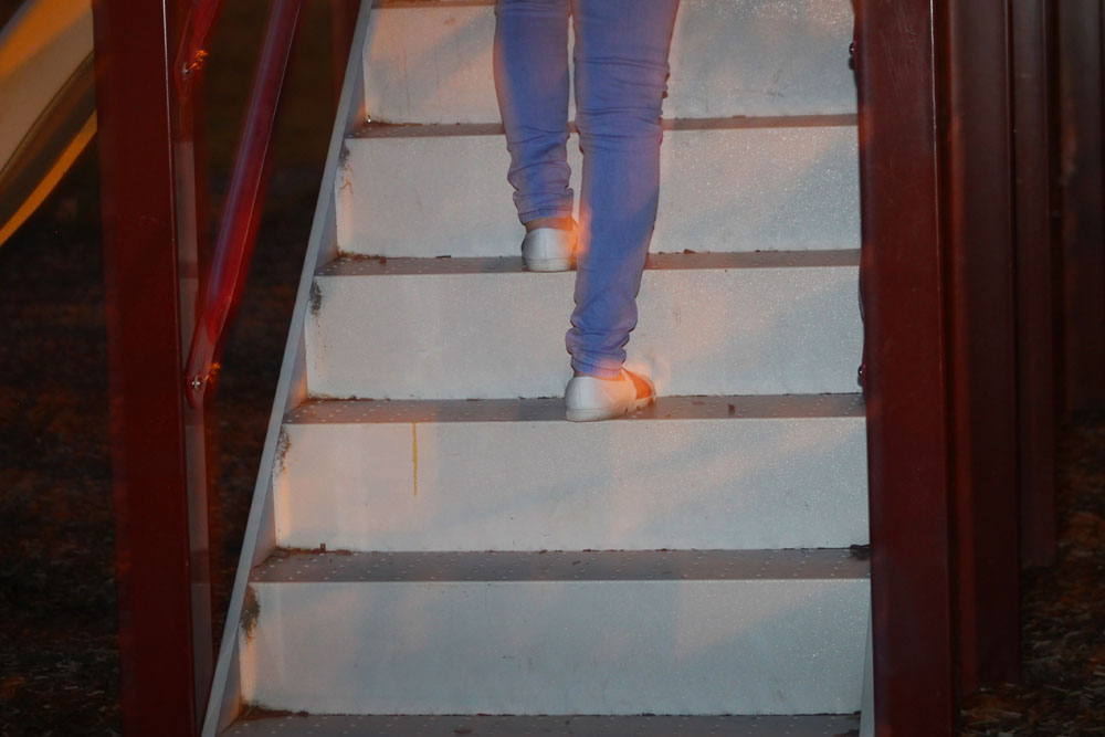 a person in blue denim and white shoes ascending white steps