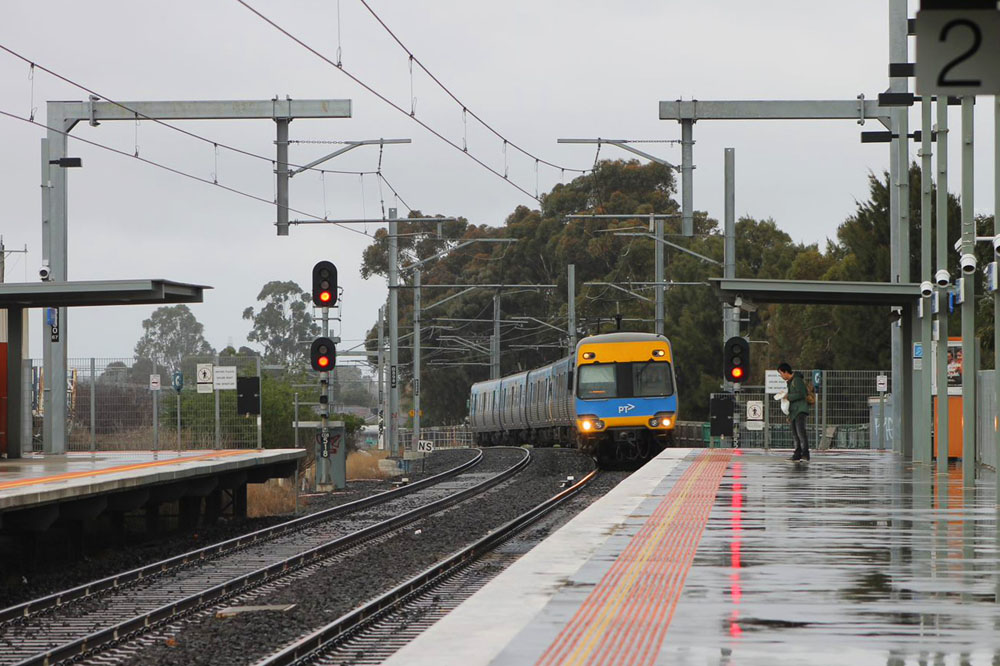a Melbourne metro train pulling into a platform on a rainy day