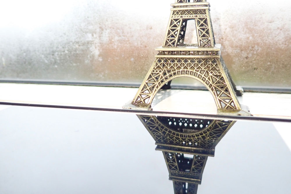 image capturing both a scale model of the Eiffel tower and its reflection