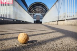 close up shot of a small wooden sphere on a deserted bridge