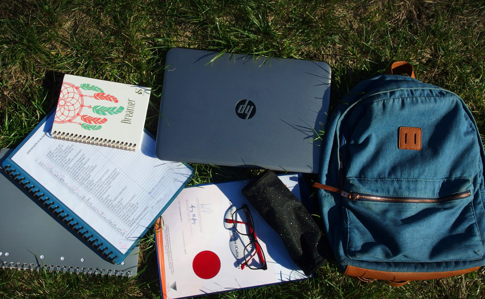 image of a backpack and its contents such as computer, notebook, stationary etc.