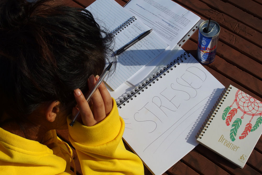 over-the-shoulder shot of a young woman who has writted 'stressed' in block capitals in her notebook