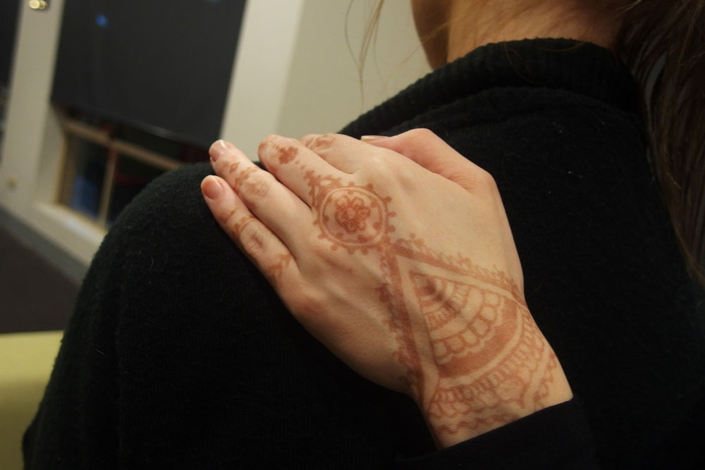 A hand with a henna tattoo is placed supportingly on a young womans shoulder