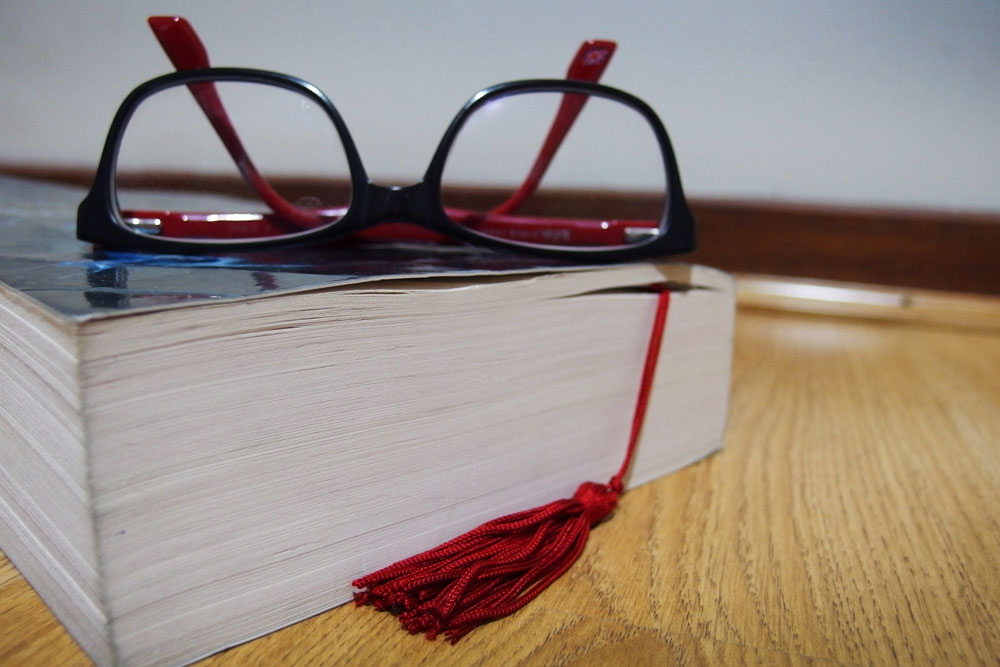 upside down spectacles lying flat on top of a closed book