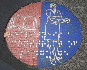 pavement mosaic of a book and a lady on either side with a message in braille