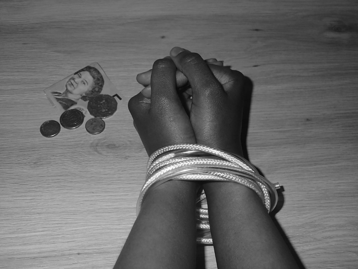 hands bound by cord are shown next to a small amount of money
