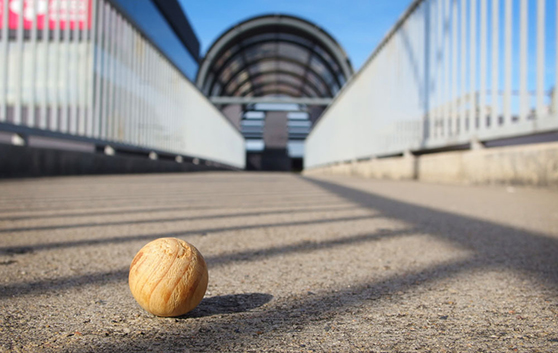 a close up shot of a small wooden sphere on an empty large bridge