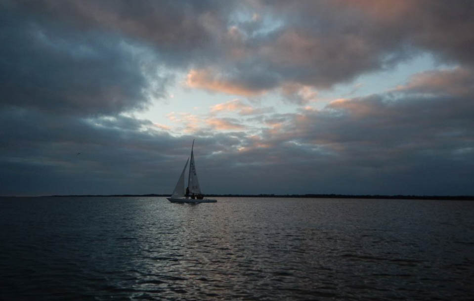 A small sailboat underneath a grey sky